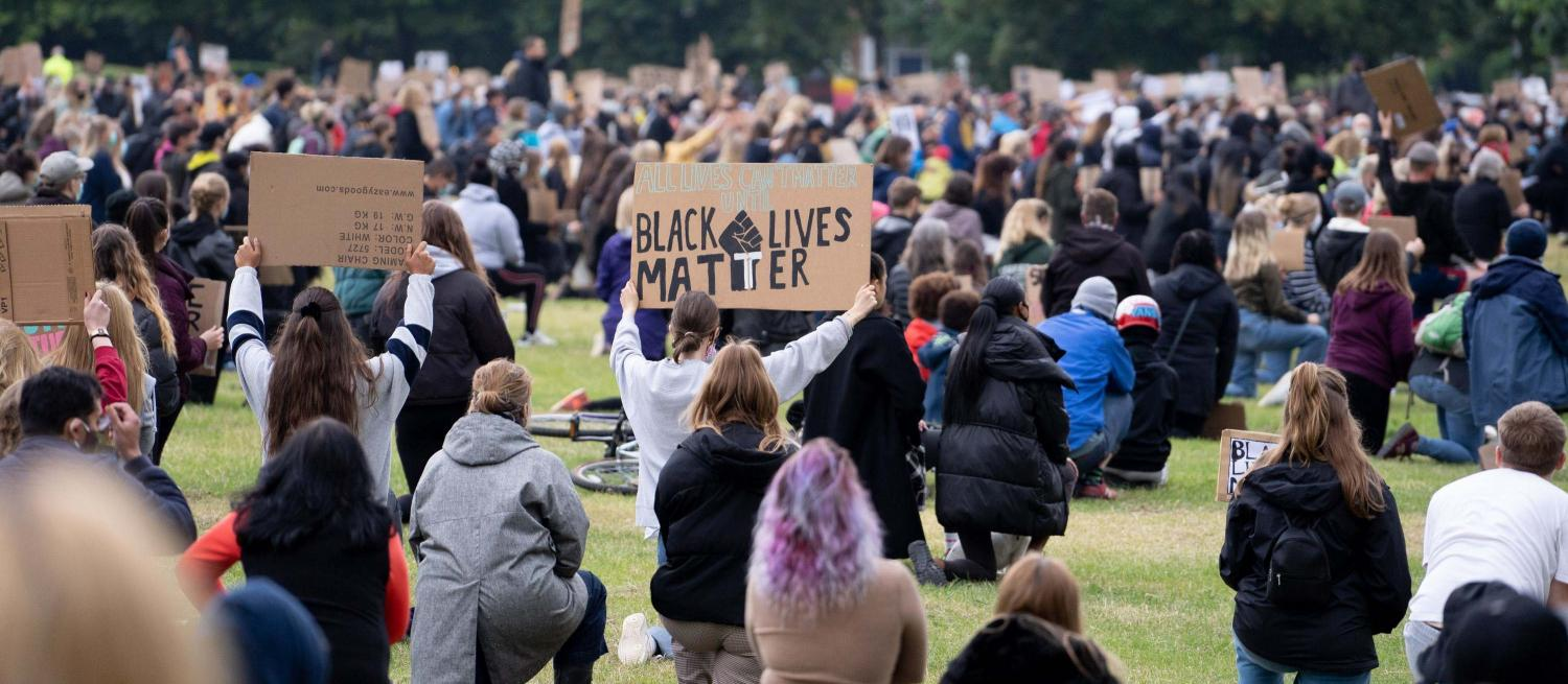 A crowd of people kneeling in a field shown from behind. One person is holding up a sign which says Black Lives Matter