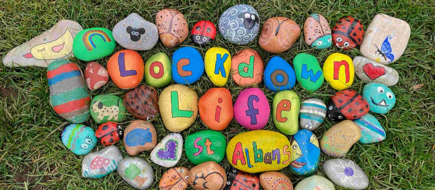 Lockdown Life St Albans painted onto rocks surrounded by colourful painted rocks