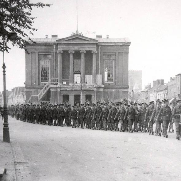 Soldiers marching in front of the old Town Hall during the First World War